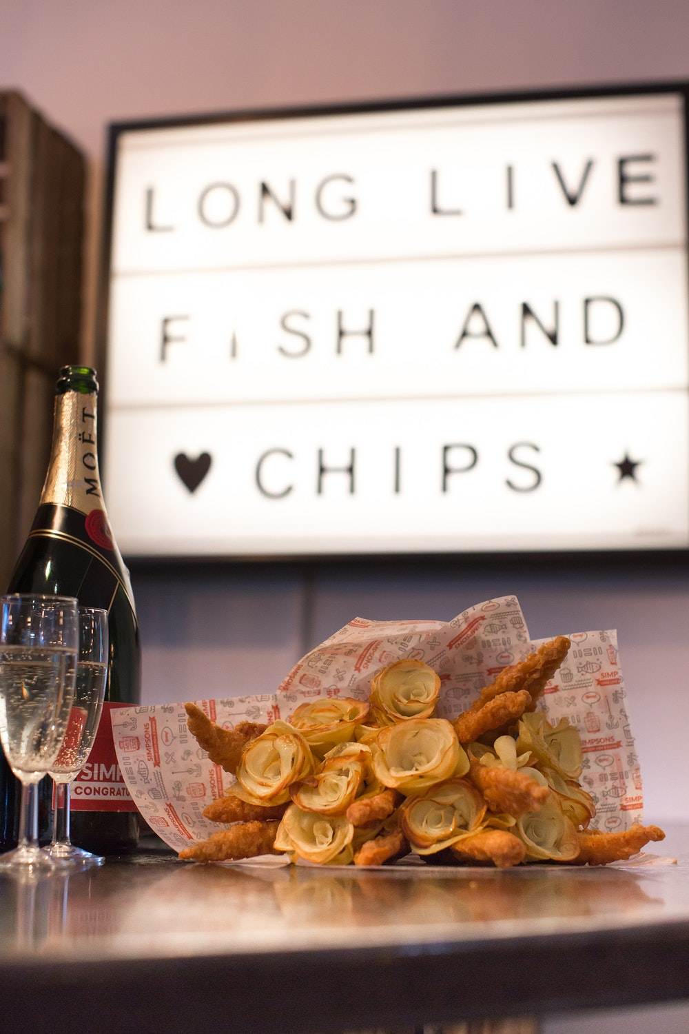 fish and chip bouquet with champagne bottle and glasses