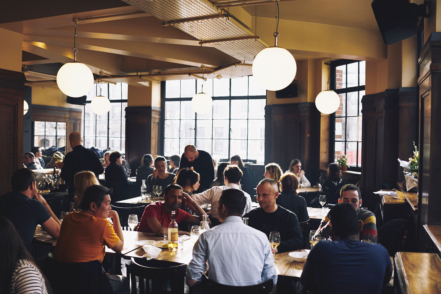 a crowd of people sat at tables in Brat restaurant in Shoreditch London
