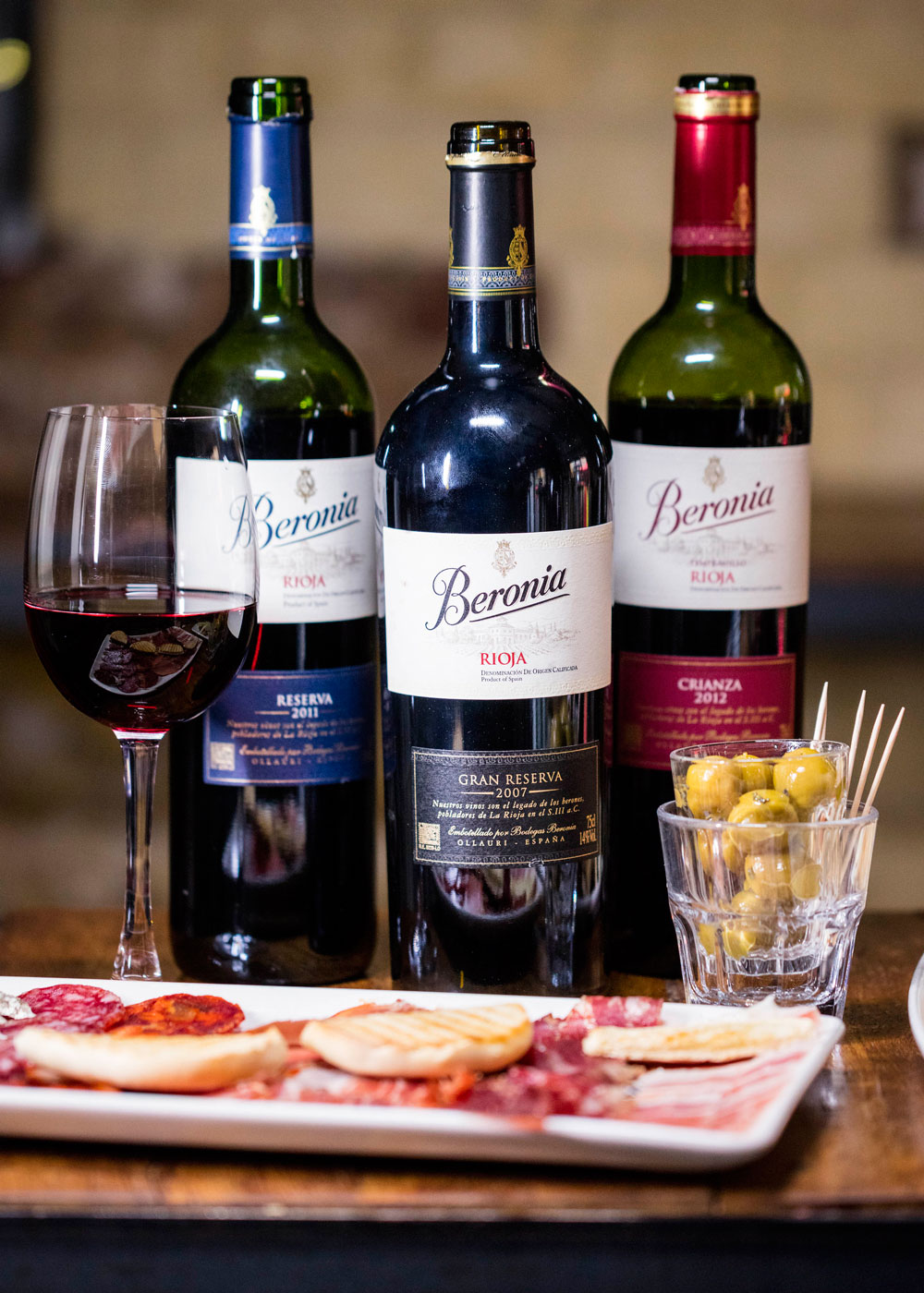Beronia wine bottles on table with tapas sliced meats