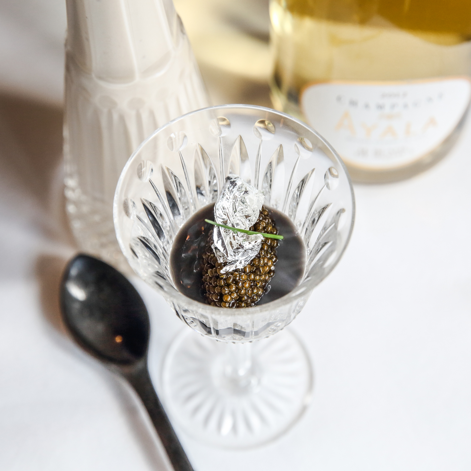 Helene Darroze chef in restaurant with caviar dish and wine