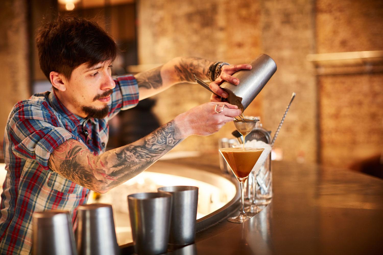 Sophie's Soho bartender mixing drink
